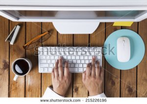 stock-photo-businesswoman-using-pc-computer-on-her-office-table-215226196